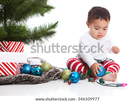 Christmas!  Adorable mixed race baby boy wearing pajamas and sitting next to the Christmas tree with presents, lights and Christmas bulbs.  Isolated on white.  - stock photo