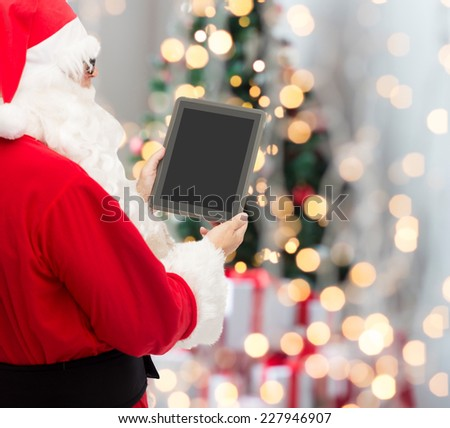 christmas, advertisement, technology, and people concept - man in costume of santa claus with tablet pc computer over tree lights background - stock photo