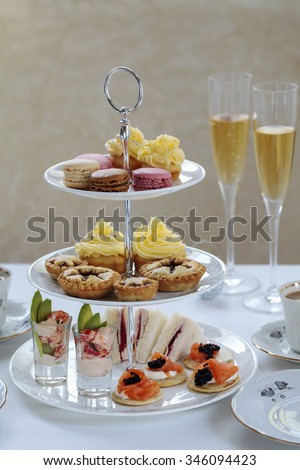 Christmas afternoon tea with turkey and cranberry sandwiches, crayfish cocktails, salmon blinis, mince pies, cupcakes and macaroons - stock photo