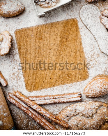 Christmas and holiday baking, cookies, flour, spruce branches and square space for text on a wooden board, ready template - stock photo