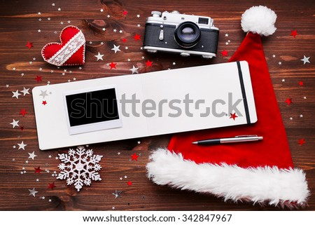 Christmas and New Year background with old fashioned camera, red Santa's hat, notepad, photo frame and decorations - stars, silver sparkling snowflakes, confetti on wood. Place for your text. Mock up. - stock photo