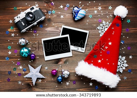 Christmas and New Year background with old fashioned camera, red Santa's hat, photo frames and christmas decorations - stars, silver snowflakes, confetti on wooden table. Place for your text. Mock up. - stock photo