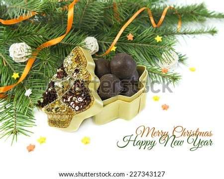 Christmas and New Year card with sample text, open decorated gift box full of round chocolate candies and with natural conifer branches, isolated on white - stock photo