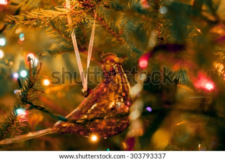 Christmas and New Year decoration. Beautiful gold bird bauble and lanterns are hanging on the Christmas tree. Holiday glowing background. - stock photo