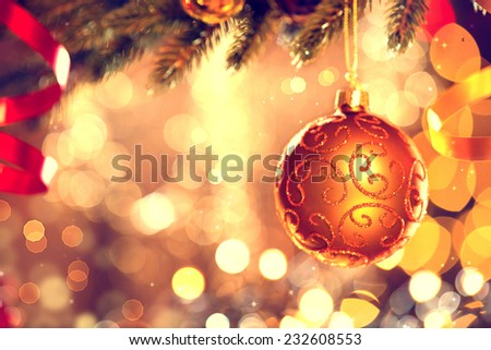 Christmas and New Year Decoration. Golden Bauble hanging on Christmas Tree. Holiday Glowing Background. Shallow DOF  - stock photo