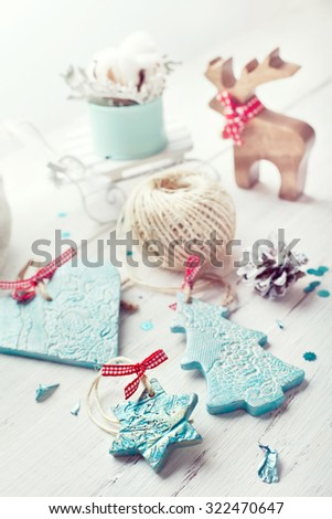 Christmas and New Year decorations - candles, hand made ceramic decor (heart, tree and star) and wooden reindeer, on wooden table. Lightly toned photo.  - stock photo
