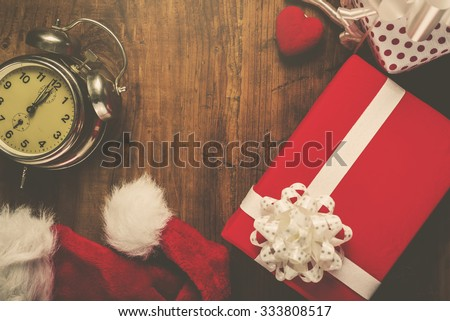 Christmas and New Year holiday, Santa Claus hat, presents, gifts and vintage clock at midnight, top view, retro filter toned image - stock photo