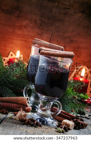 Christmas and New Year mulled wine with cinnamon, cardamom and anise on a background of spruce branches, snowflakes and burning candles, dark toned image, selective focus - stock photo
