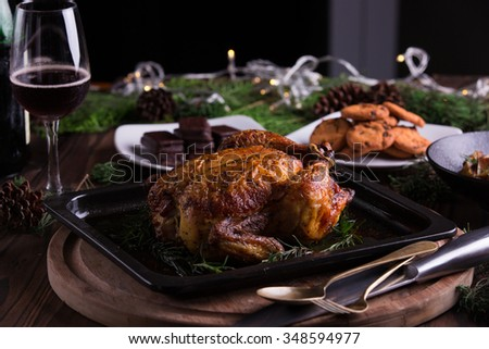 Christmas and new year's eve dinner: roasted whole chicken / turkey, sauteed cubed sweet potato, chocolate chip cookies, chocolate coated biscuits, and red wine - stock photo