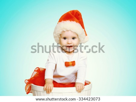 Christmas and people concept - happy smiling baby in santa red hat gets out of the container - stock photo