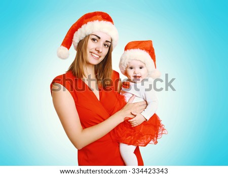 Christmas and people concept - happy smiling mother and baby in santa red hats  - stock photo
