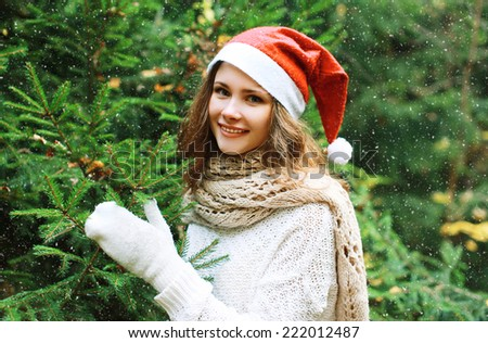 Christmas and people concept - happy young girl in winter hat near tree  - stock photo