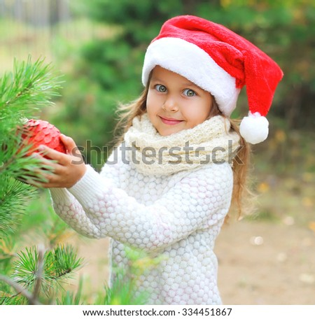 Christmas and people concept - little child in santa red hat with ball - stock photo