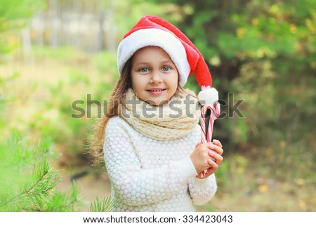 Christmas and people concept - portrait little girl child in santa red hat with sweet lollipop cane  - stock photo