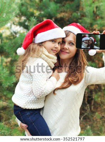Christmas and technology concept - mother and child taking picture self portrait on smartphone together - stock photo