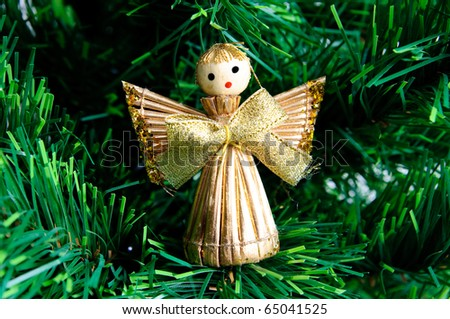 Christmas angel made from straw on xmas green tree - stock photo