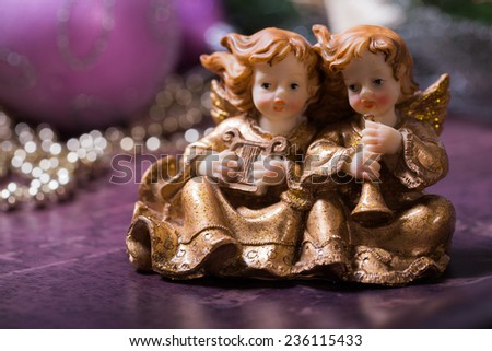Christmas angels singing and playing on the harp and trumpet. Christmas green wreath and purple, pink Christmas Balls with golden, shiny Christmas chain on the background. - stock photo