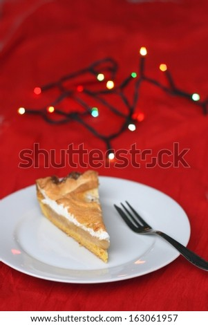 Christmas apple pie with whipped egg white, christmas lights in the background, shallow DOF - stock photo