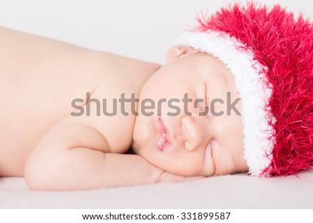 Christmas baby: beautiful newborn baby sleeping on a blanket, with Santa hat.  - stock photo