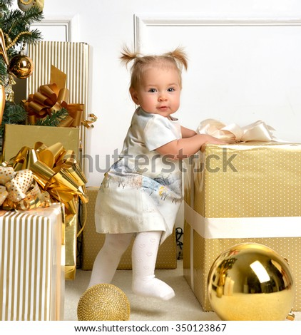 Christmas baby child toddler near gold christmas tree presents and ball decoration near present gift box. New Year 2016 holiday concept isolated on a white background - stock photo