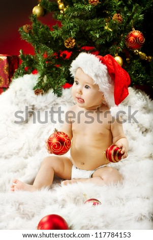 Christmas baby in hat sitting on fur holding red ball near new year fir tree - stock photo