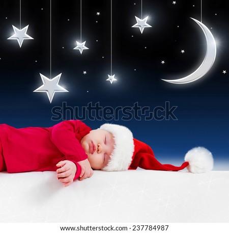 Christmas baby is sleeping on background fairy-tale night - stock photo