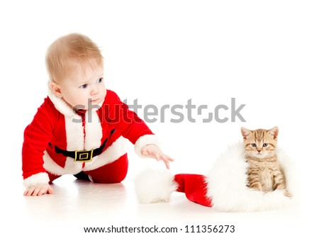 christmas baby reaching out hand for cat in a santa claus hat - stock photo