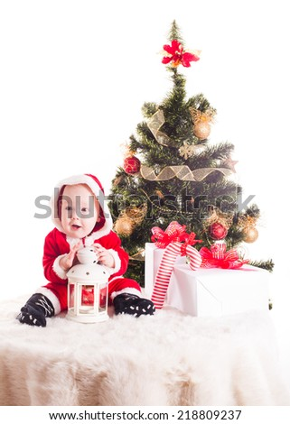 Christmas baby under the New Years tree with gifts - stock photo
