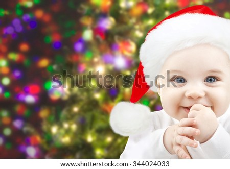 christmas, babyhood, childhood and people concept - happy baby in santa hat over holidays lights background - stock photo