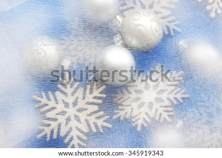 Christmas background: bauble and decorative snowflakes on satin fabric - stock photo