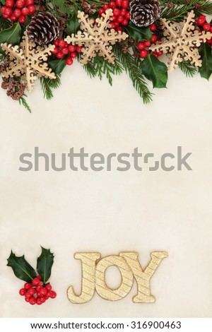 Christmas background border with gold joy sign, snowflake bauble decorations, holly and winter greenery over old parchment paper. - stock photo