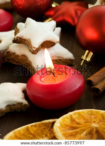 Christmas background candle, cinnamon star cookies, spices and ornamets. Shallow dof. - stock photo