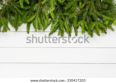 Christmas background. Christmas fir tree on white wooden board background with copy space.   - stock photo