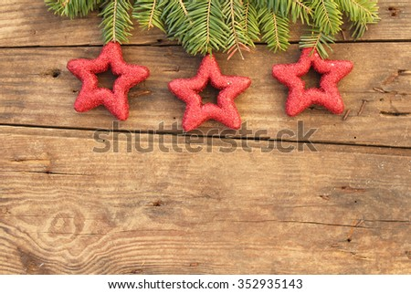 Christmas background - Christmas ornaments in star shape on fir tree - on wooden background - copy space - border design - stock photo