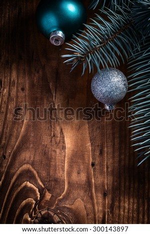 christmas background fir tree branch and balls on wood board. - stock photo