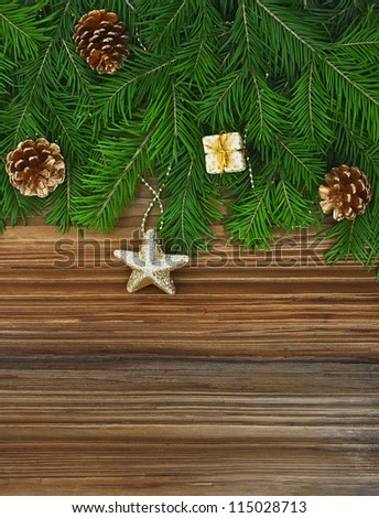 Christmas background: fir-tree branches with Christmas tree decorations on an old wooden background - stock photo