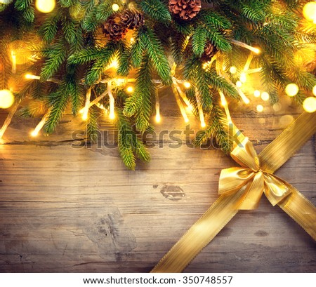 Christmas Background. Fir tree with decoration on wooden board background with golden gift bow. Border art design with Christmas tree, baubles and light garland - stock photo