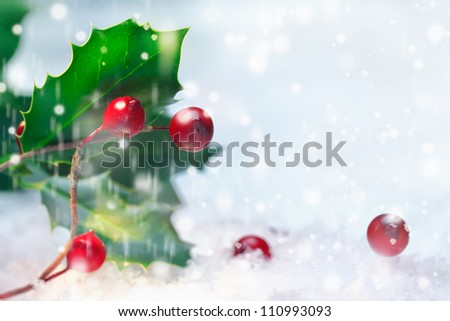 Christmas background of holly with red berries in falling snow with sparkling bokeh and copyspace - stock photo