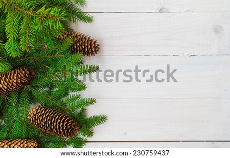 Christmas background: spruce twigs and cones on white board - stock photo