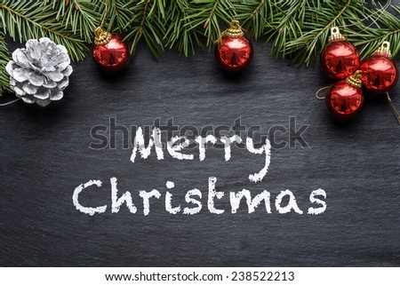 Christmas background with colorful red baubles, a silver decorative pine cone and green pine branches over a textured grey background with merry Christmas text - stock photo
