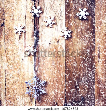 Christmas background with festive decorations and falling snow over wooden board. Vintage Christmas card or invitation with copyspace. - stock photo