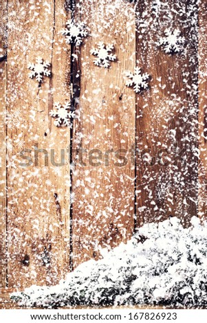 Christmas background with festive ornaments and falling snowflakes over old wooden wall. Vintage Christmas card or invitation with copyspace. - stock photo