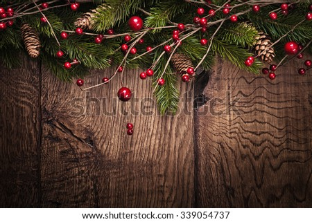 Christmas background with fir branches and berries on wood background - stock photo