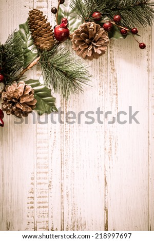 Christmas background with fir branches,pinecones and berries on the old wooden board in vintage style  - stock photo