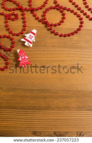 Christmas background with fir branches, red holly berries and small decorative clothespins as firsd - stock photo