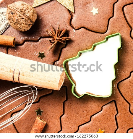 Christmas background with Gingerbread baking dough, cookie cutters, spices and nuts. Christmas festive food, top view, closeup. - stock photo