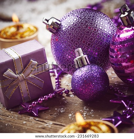 Christmas background with purple balls, golden candles and snow - stock photo