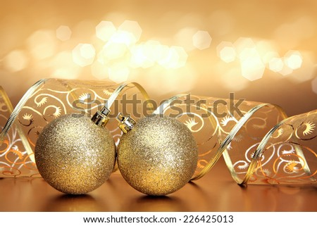 Christmas background with two golden ornaments, ribbon and bokeh  - stock photo