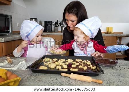 Christmas Bakery in a kitchen. Little girl and her mom working together - stock photo