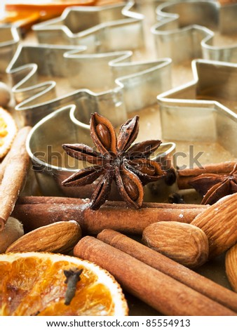 Christmas baking background dough, cookie cutters, spices and nuts. Shallow dof. - stock photo